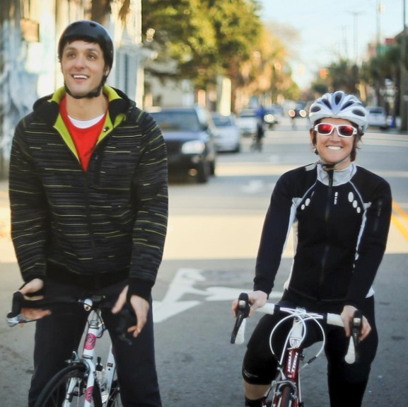 Cyclists wearing helmets and smiling